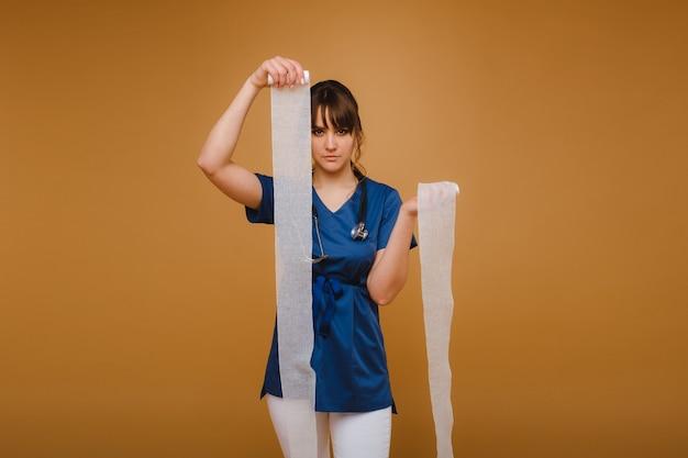 Medic femme en blouse blanche et masque tient un bandage de gaze tordu pour panser les plaies, fond blanc.