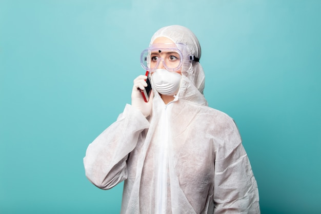 Medic femme portant des vêtements de protection contre le virus parlant par téléphone mobile