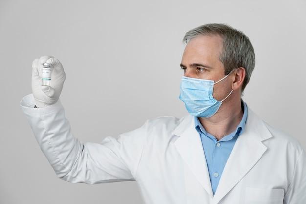 Medic avec des gants en latex tenant un flacon de vaccin