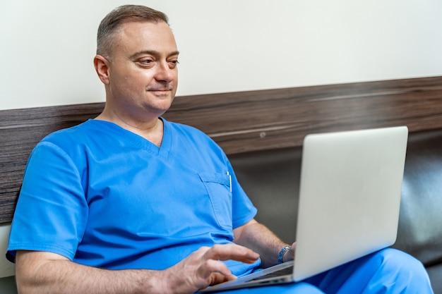 Medic en gommage sur canapé avec ordinateur portable. lecture de documents depuis l'écran.