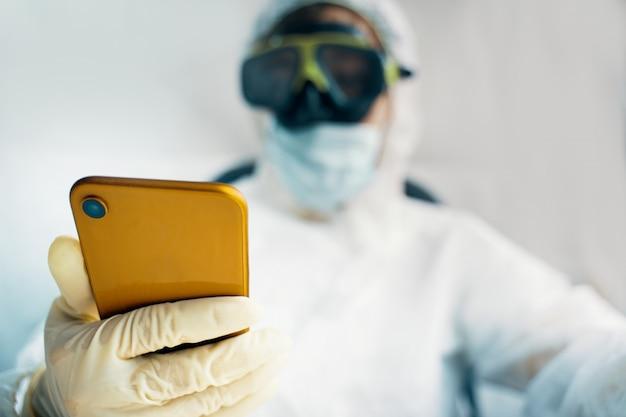 Medic en tenue de protection est en ligne avec smartphone