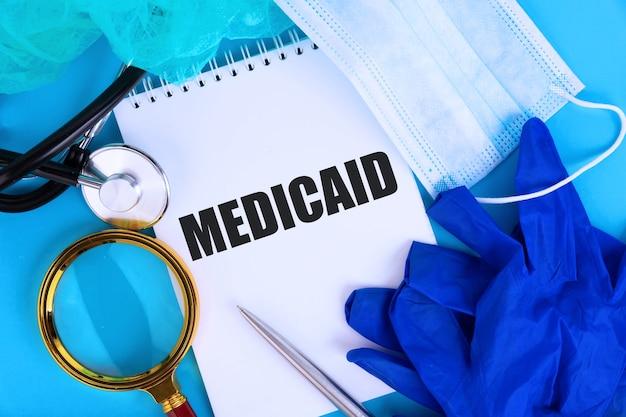 Medicaid, texte écrit dans un cahier couché sur fond bleu, avec un stéthoscope et un masque médical. concept médical.