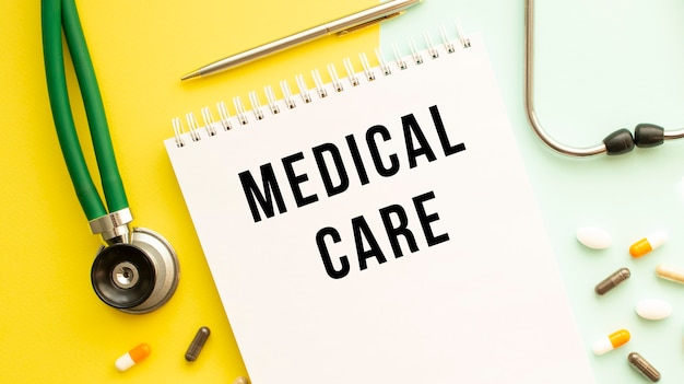 Medical care est écrit dans un cahier sur une table de couleurs à côté de pilules et d'un stéthoscope. concept médical