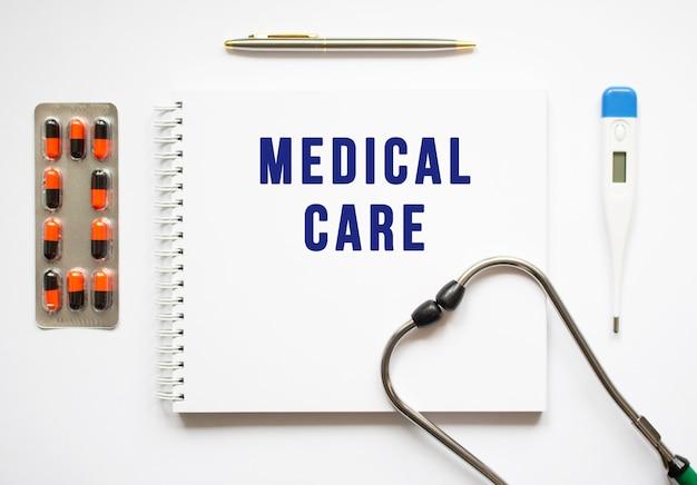 Medical care est écrit dans un cahier sur un tableau blanc à côté de pilules et d'un stéthoscope.