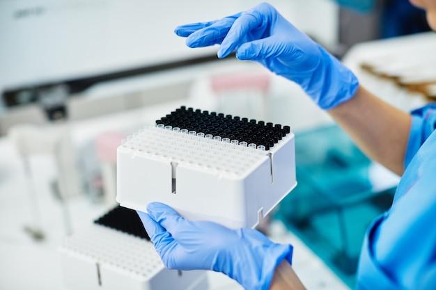 Medical scientist holding fort avec des tubes à essai de couleur noir et blanc au laboratoire