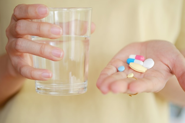 Médicament et eau dans la main d'une femme pour manger pour traiter la maladie. concept de soins de santé.