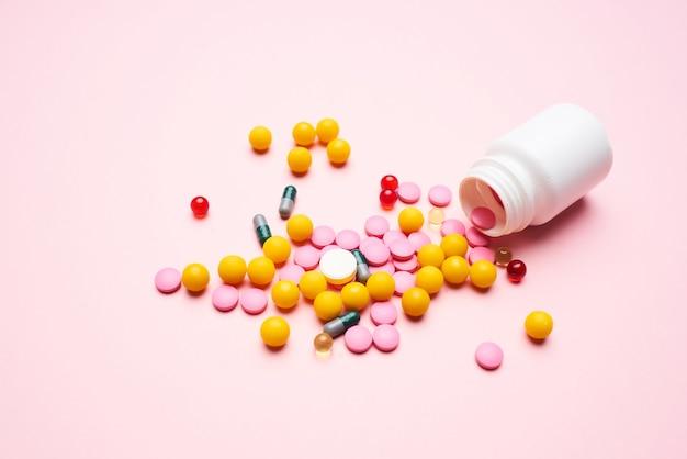 Médicament saupoudré d'un pot sur un fond rose de produits pharmaceutiques en gros plan