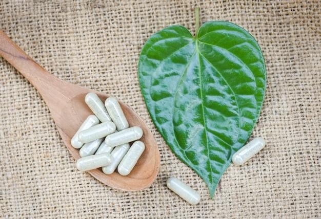 Médicaments à base de plantes / capsules d'herbes naturelles sur une cuillère en bois et des feuilles vertes sur fond de sac