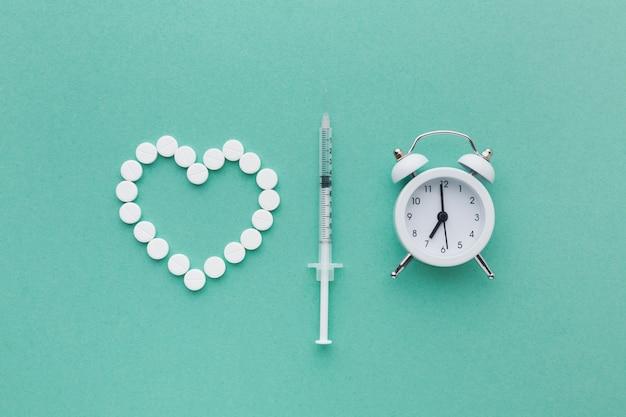 Médicaments blancs médicaux et horloge blanche avec seringue