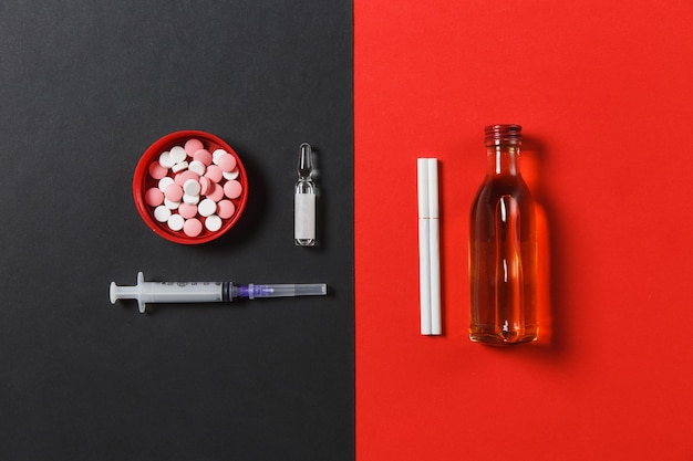 Médicaments comprimés colorés comprimés résumé, aiguille de seringue vide, bouteille avec alcool cognac, whisky, ampoule, cigarettes
