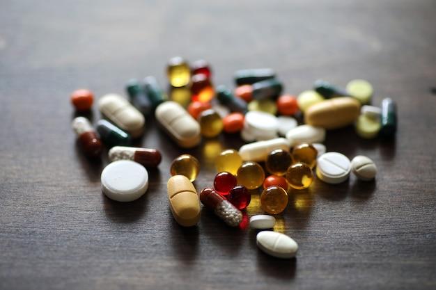 Médicaments et comprimés de différentes couleurs sur une table de texture en bois