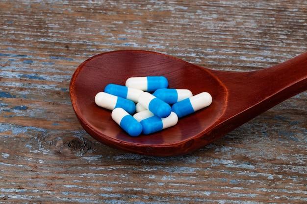 Médicaments, comprimés et gélules sur cuillère en bois.