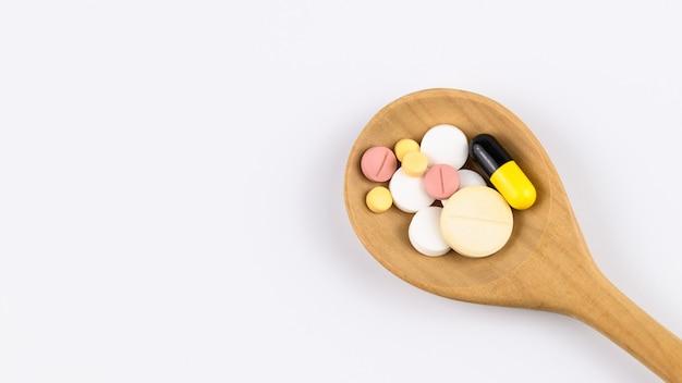 Médicaments, comprimés, pilules et capsules renversant une cuillère en bois.