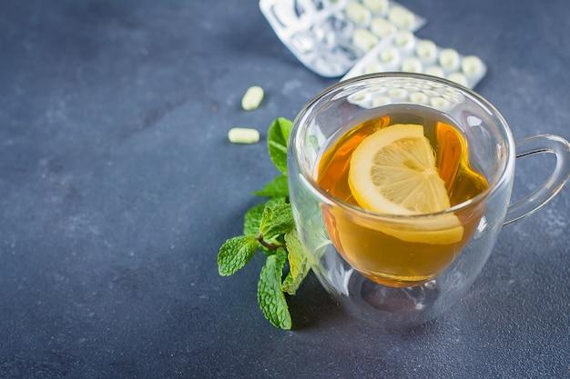 Médicaments et concept de soins de santé. tasse de thé chaud aux citrons, pilules et thermomètre