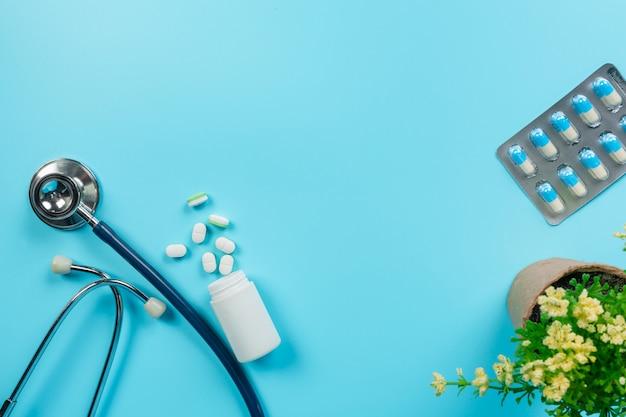 De médicaments, fournitures médicales placées avec des outils de médecin sur un bleu.