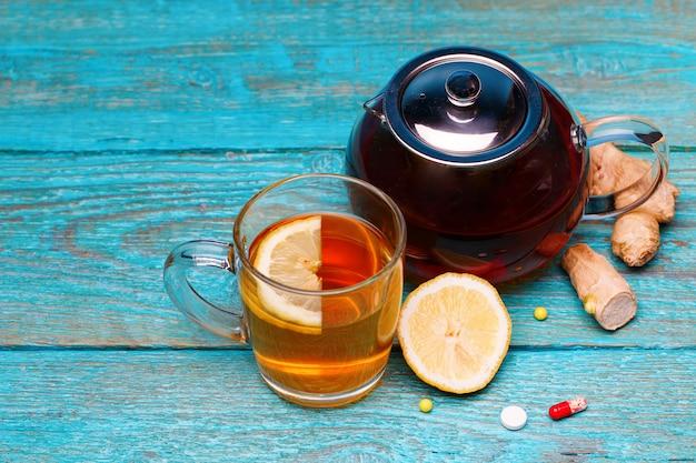 Médicaments froids, thé, citron et gingembre sur bleu en bois
