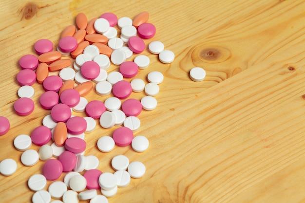 Médicaments pharmaceutiques assortis, comprimés sur une table en bois