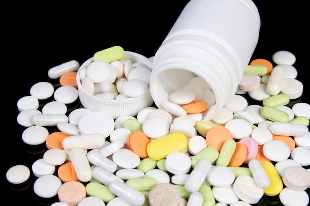 Les médicaments et les pilules sont dispersés sur un tableau noir