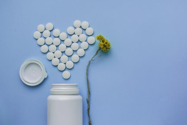Les médicaments sont des pilules rondes blanches avec un noyau, isolées sur un fond violet.