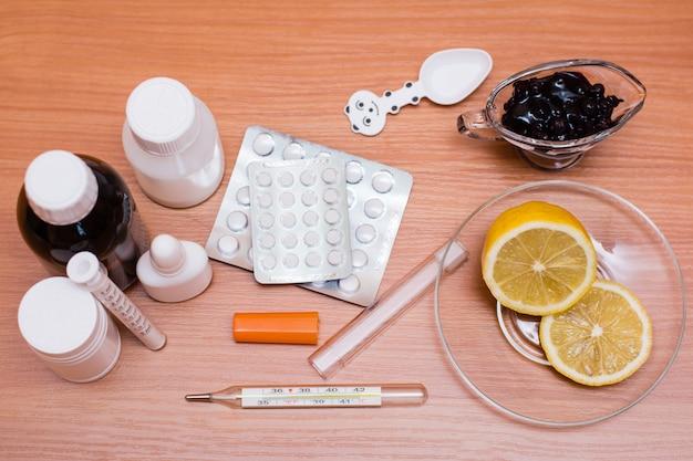 Médicaments, thermomètre, citron et confiture sur la table. vue de dessus