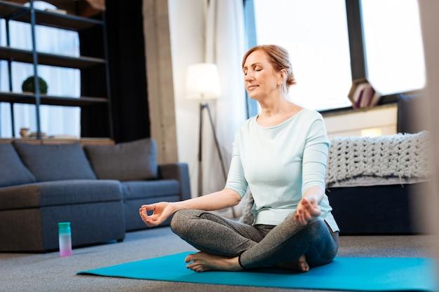 Méditation du matin. belle femme tranquille méditant avec les yeux fermés tout en ayant connecté le bout des doigts