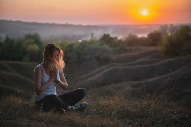 Méditation femme ou prier au coucher du soleil