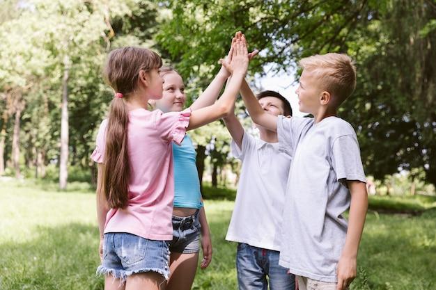 Medium shot kids high fiving avant un match