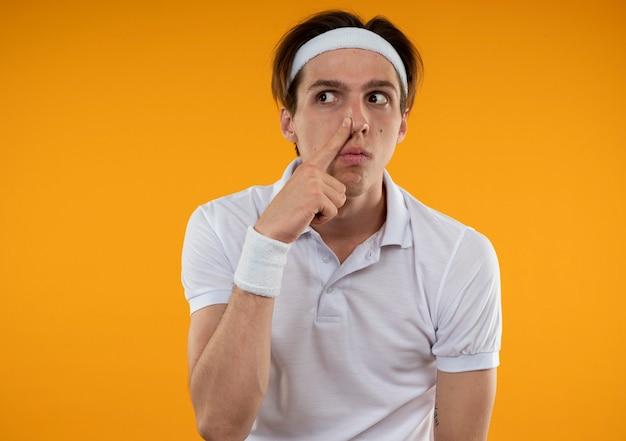 Méfiant jeune mec sportif regardant côté portant un bandeau et un bracelet mettant le doigt sur le nez isolé sur un mur orange