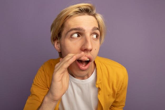 Méfiant regardant côté jeune mec blond portant des chuchotements t-shirt jaune isolés sur violet