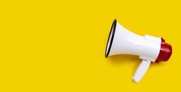 Mégaphone rouge et blanc sur fond jaune.