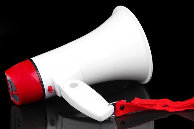 Mégaphone rouge et blanc isolé sur fond noir