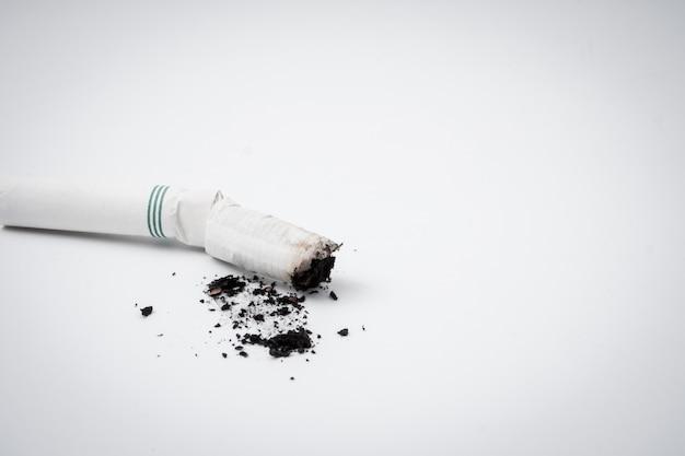 Mégot de cigarette avec de la cendre sur un fond blanc. espace libre pour le texte