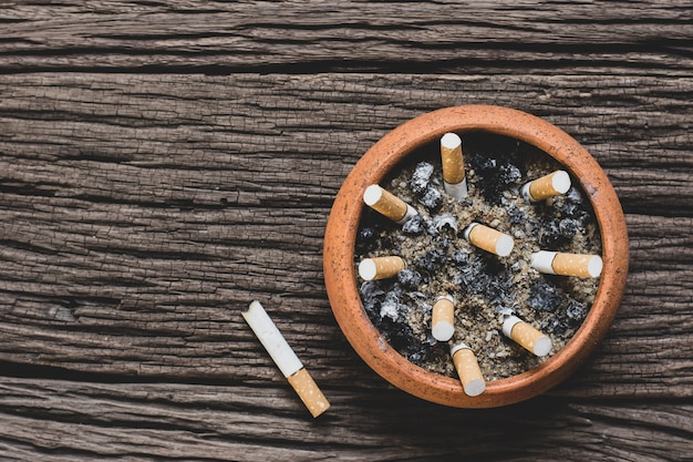 Le mégot de cigarette dans le pot est placé sur un vieux plancher en bois.