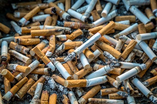 Mégots de cigarettes avec des cendres dans le cendrier, zone fumeurs / vie malsaine