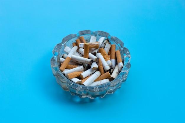 Mégots de cigarettes dans un cendrier en verre sur mur bleu.