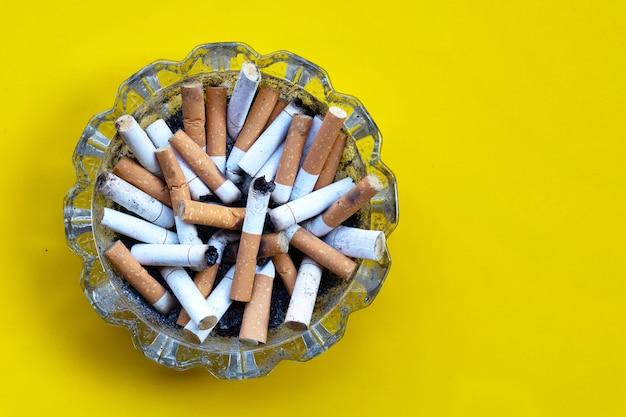 Mégots de cigarettes dans un cendrier en verre