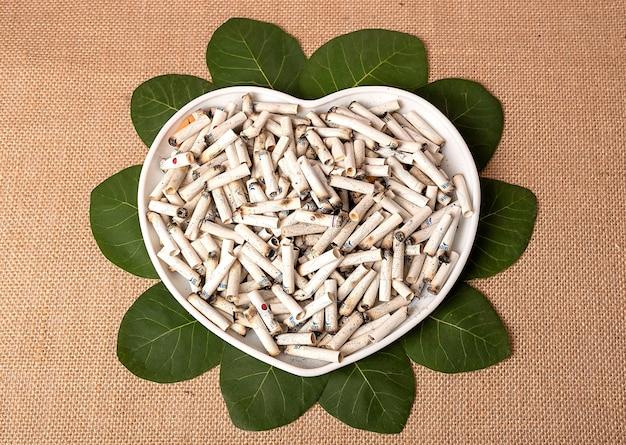 Mégots de cigarettes sur une plaque blanche en forme de coeur. la plaque repose sur les feuilles. fond de toile de jute.