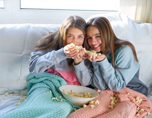 Meilleur ami filles au canapé s'amuser avec pop-corn