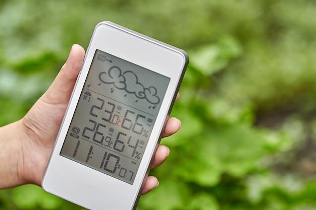 Meilleur appareil de station météo personnelle avec des conditions météorologiques à l'intérieur et à l'extérieur. une fille tient un gadget à la main sur un fond de feuillage vert.