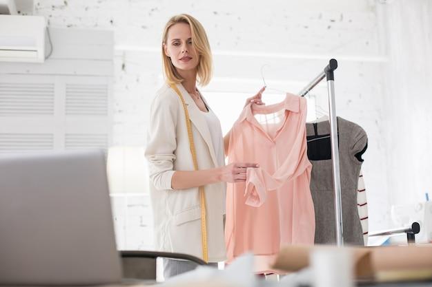 Meilleur choix. faible angle de couturier féminin attrayant regardant l'écran tout en tenant le vêtement