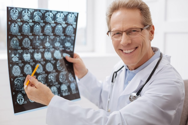 Meilleur dans mon domaine. beau joyeux expert distingué étudiant l'analyse du cerveau qu'il tient dans sa main tout en déterminant le diagnostic des patients