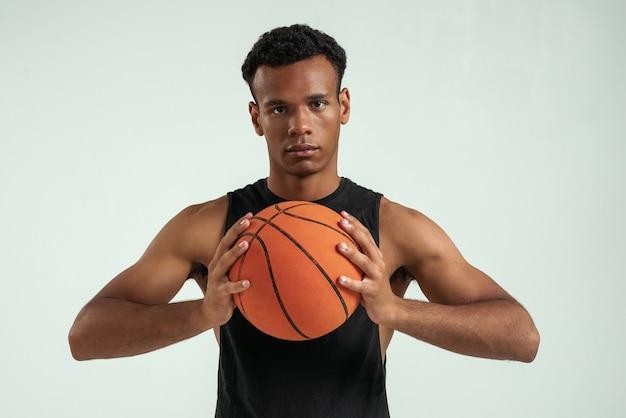 Meilleur jeu beau jeune homme africain tenant un ballon de basket et regardant la caméra en se tenant debout