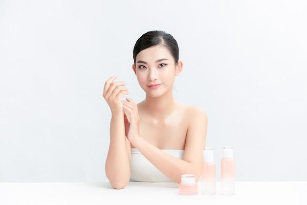 Meilleur produit. jeune femme assise à une coiffeuse contre un mur blanc et montrant un produit cosmétique avec le sourire