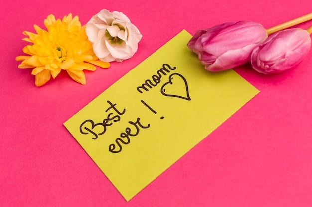 Meilleur titre de maman sur papier jaune avec des boutons de fleurs