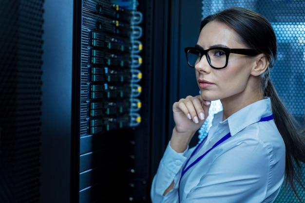 Meilleur travail. femme méditative sérieuse travaillant avec l'équipement et la pensée