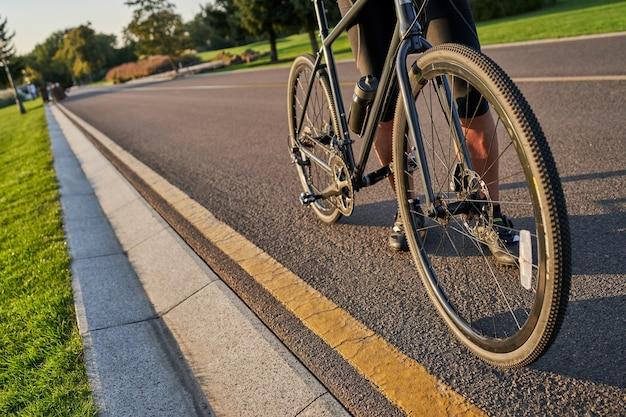 Meilleur véhicule. photo détaillée recadrée d'un cycliste faisant du vélo de course le long d'une route goudronnée dans le parc.