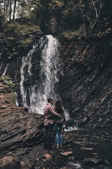 Meilleur voyage. vue arrière sur toute la longueur du jeune couple embrassant tout en se tenant près de la cascade