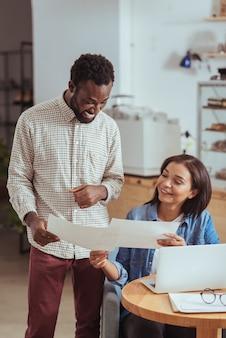 Meilleure collaboration. agréable jeune femme et son joyeux collègue masculin regardant à travers les documents de leur projet de démarrage tout en en discutant dans le café