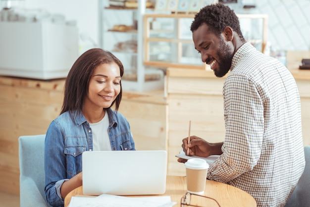 Meilleure coopération. jolie jeune femme assise dans le café avec son collègue masculin et travaillant avec lui sur leur projet commun pendant que l'homme prend des notes