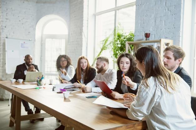 Meilleure équipe. groupe de jeunes professionnels ayant une réunion. un groupe diversifié de collègues discute de nouvelles décisions, plans, résultats, stratégie. créativité, lieu de travail, affaires, finance, travail d'équipe.